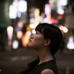 夜の繁華街を背景にポートレート撮影